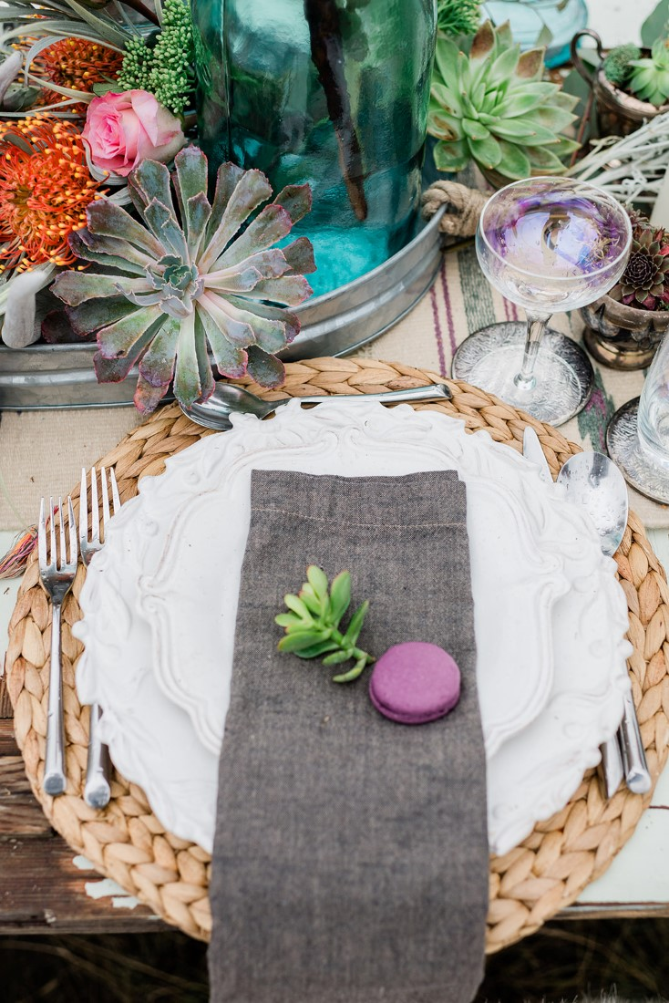 White plate sits on grass charger with succulents sitting on black linens