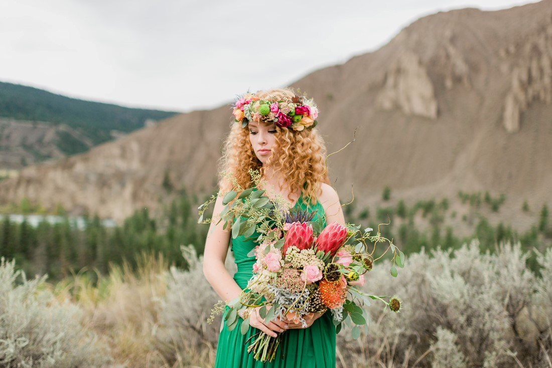 Red haired bride in emerald green dress holds bouquet of colourful flowers