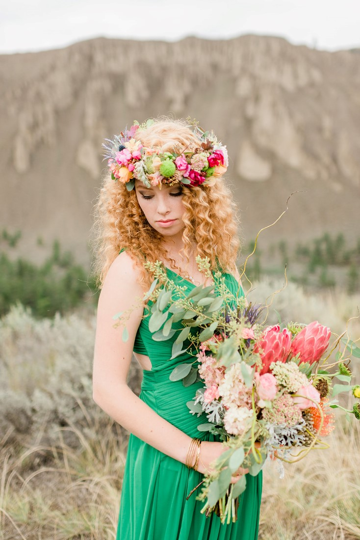 Bride in emerald green dress holds bouquet and wers floral head wreath