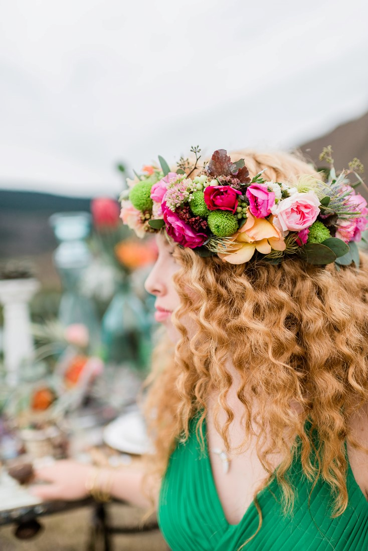 Bride in green dress has colourful floral wreath in her red hair