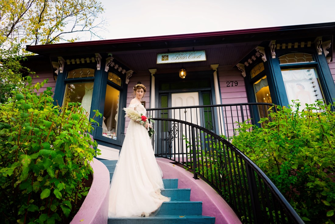 Bride stands on the painted steps of The Bride's Closet by Janayh Wright Photography