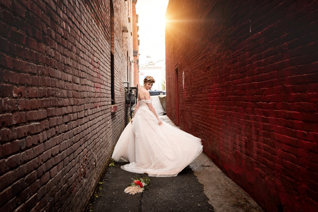 Bride in the allwy tweirling her gown by West Motion Media