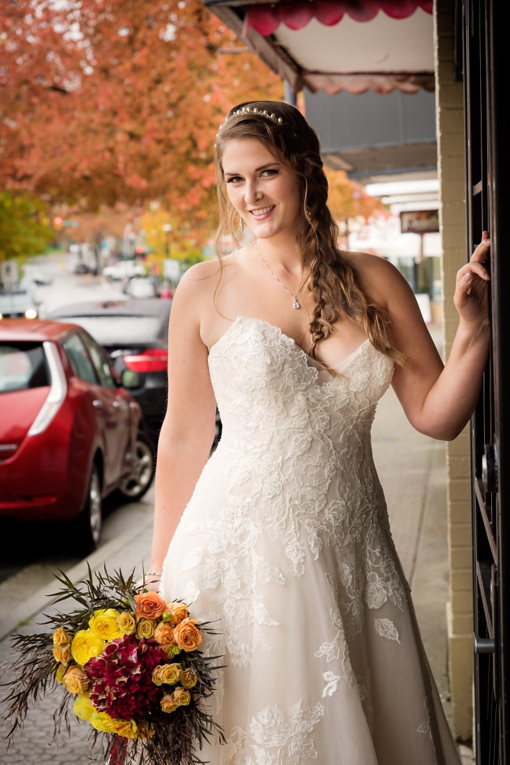 Bride poses in strapless ballgown holding orange, yellow and red bouquet