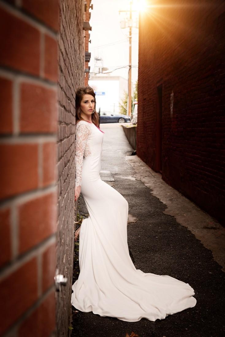 Bride poses against brick wall