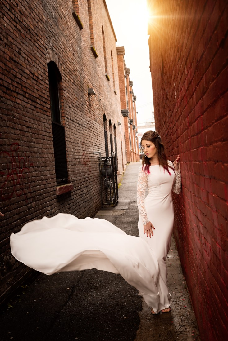 Bride in fitted gown and train flowing in alley