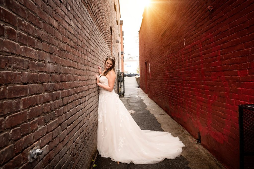 Bride stands in allwy with sunshine behind her