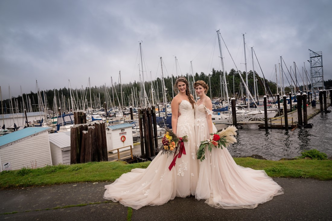 Brides pose in front of boats in Nanaimo marina