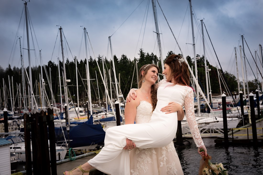 Bride lifts fellow bride in her arms in front of Nanaimo marina
