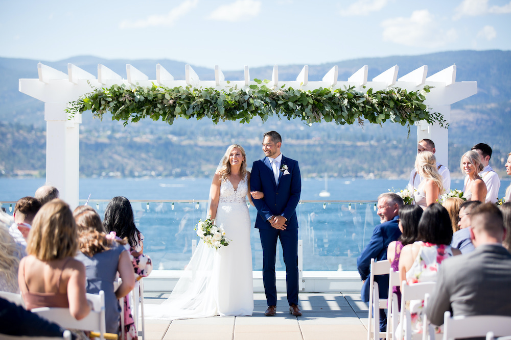 Wedding couple hold ceremony in the sunshine on lake pier with blue skies behind in Okanagan