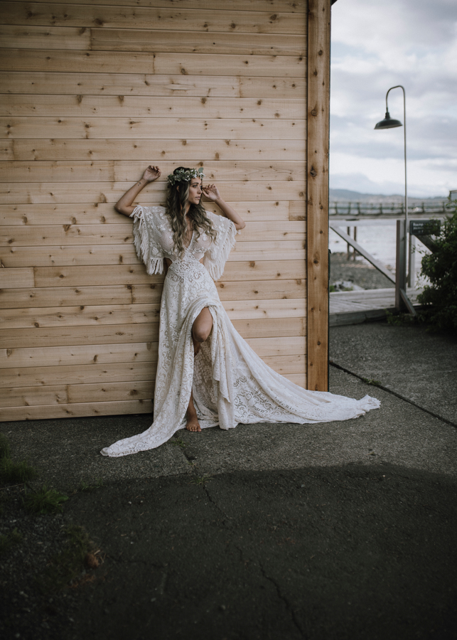 Bride against Dolphin's Resort wall in flowing lace Reclamation gown