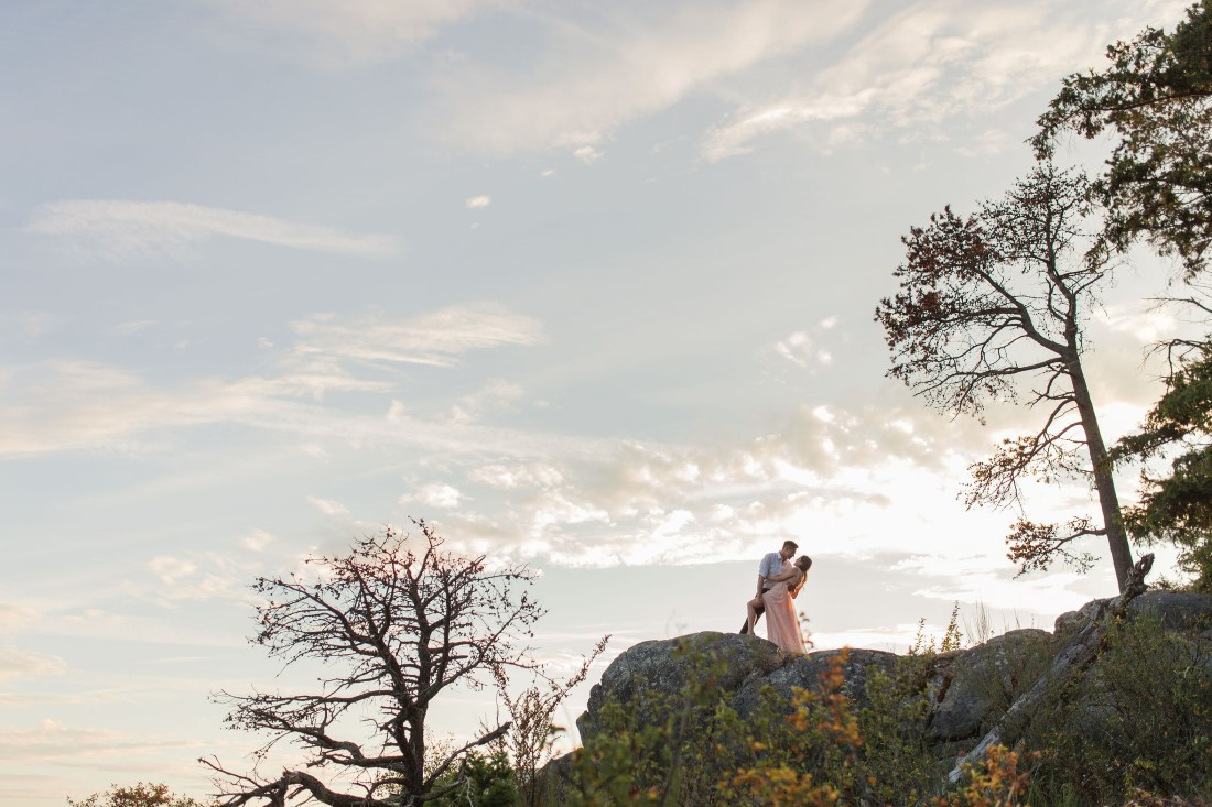 Engaged couple kiss at the top of hill with ocean sunset behind them