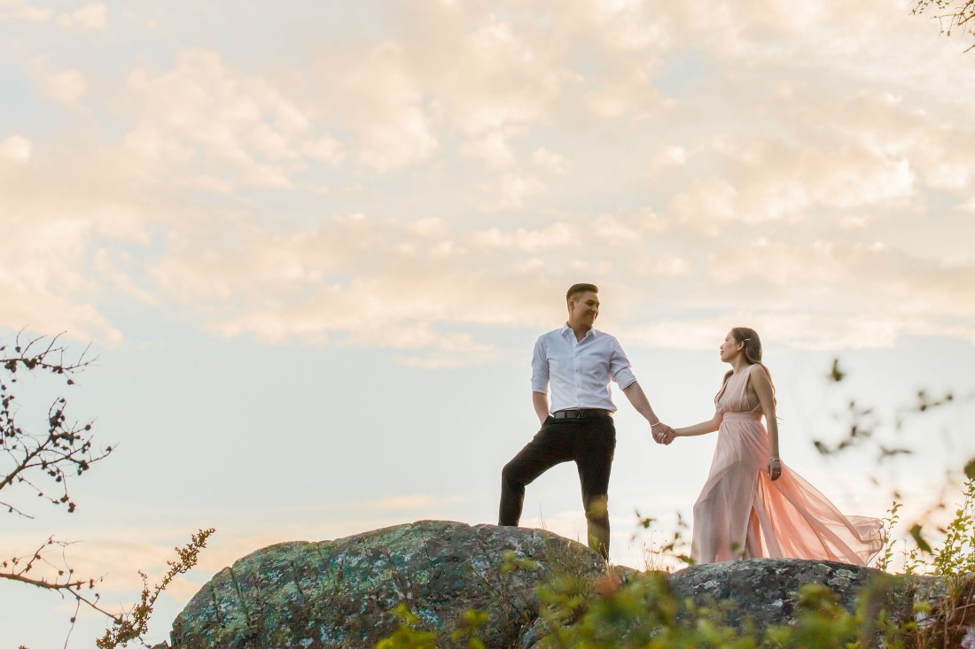 Couple holding hands climb hill with sunset behind by Vivian Ng