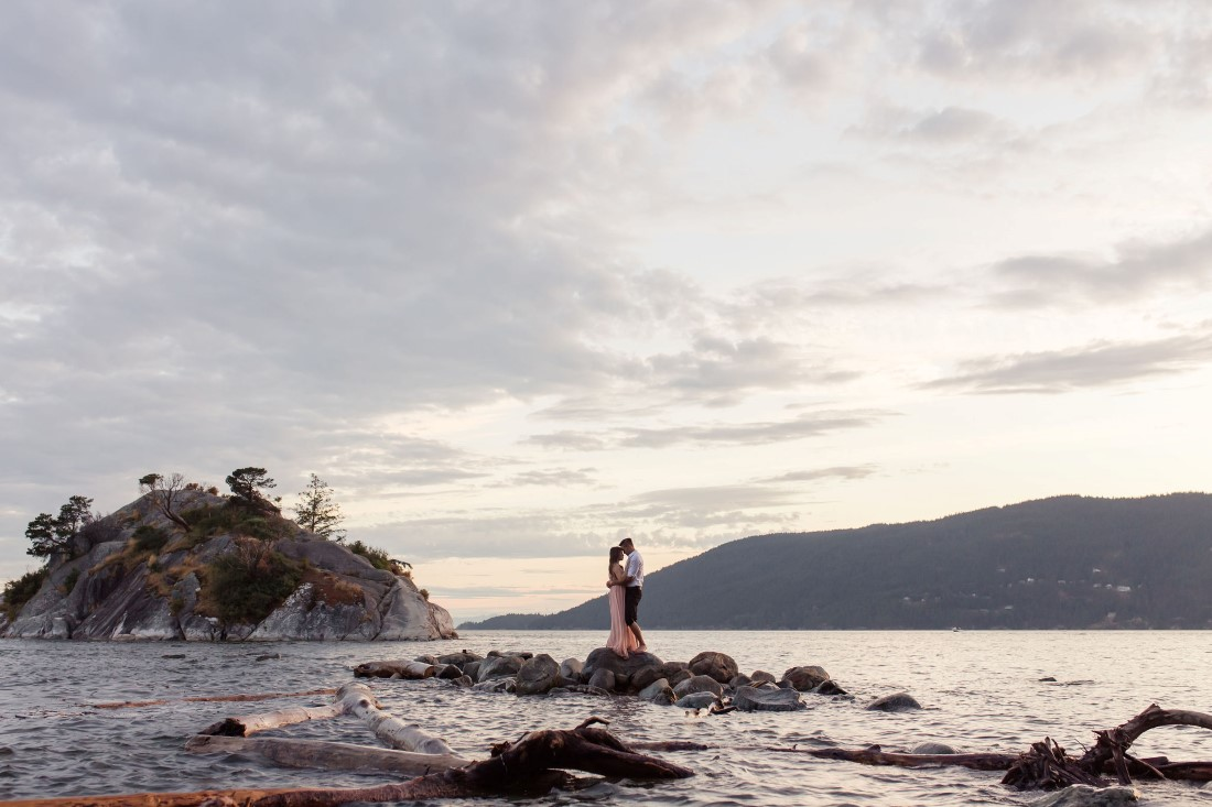 Couple in love pose on rocks in water with ocean sunset behind them in Vancouver