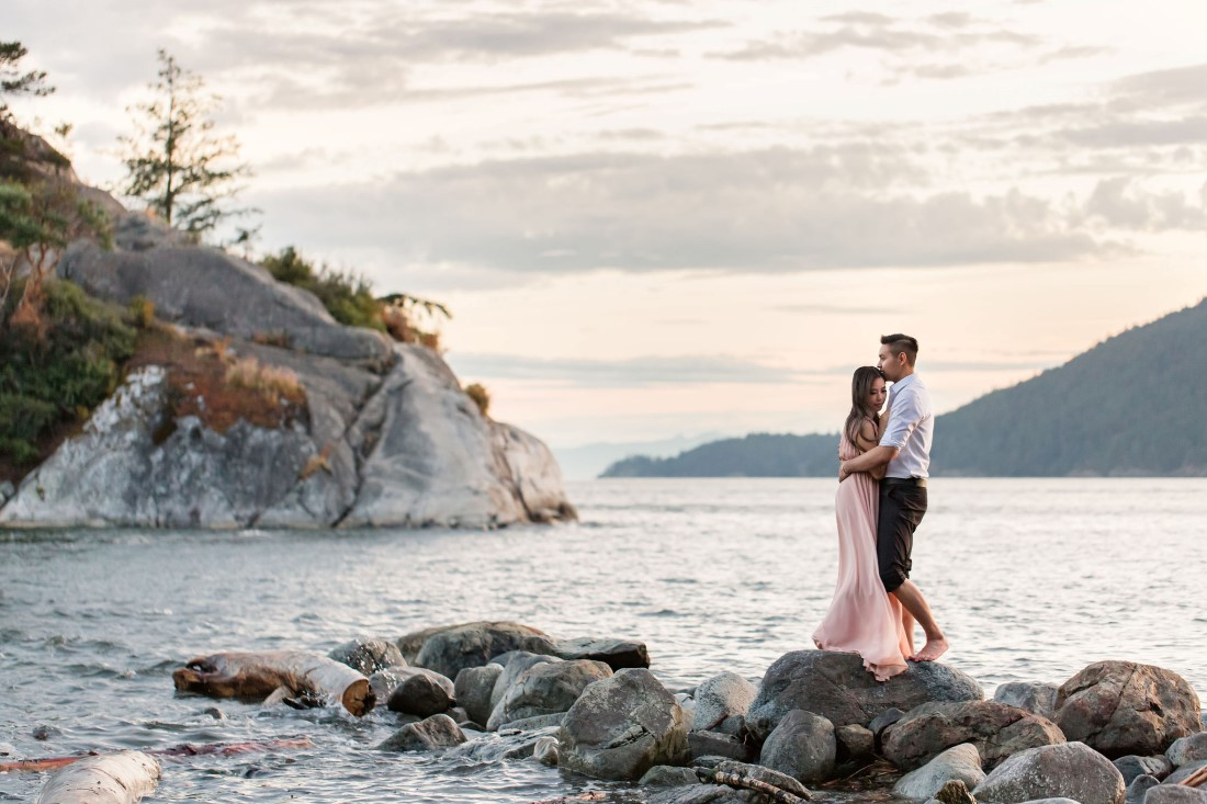Engaged couple pose on beach rocks with ocean behind them