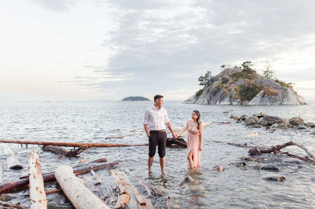 Whytecliff Park Engagement couple walk through the waves along Vancouver beach