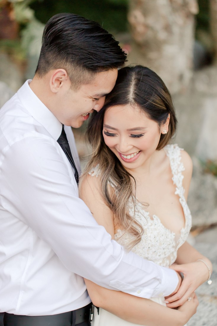 Bride to be wears long blush gown with lace top and smiles at fiance wearing white shirt and blue tie