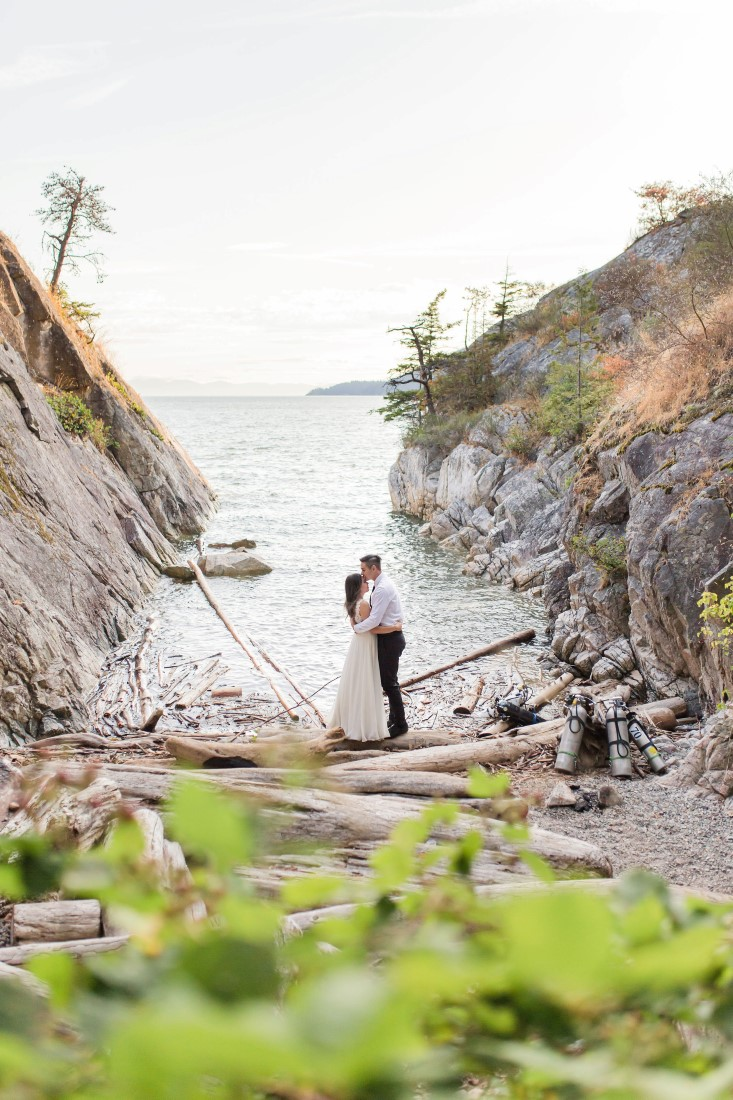 Engaged couple embrace at water inlet in Vancouver