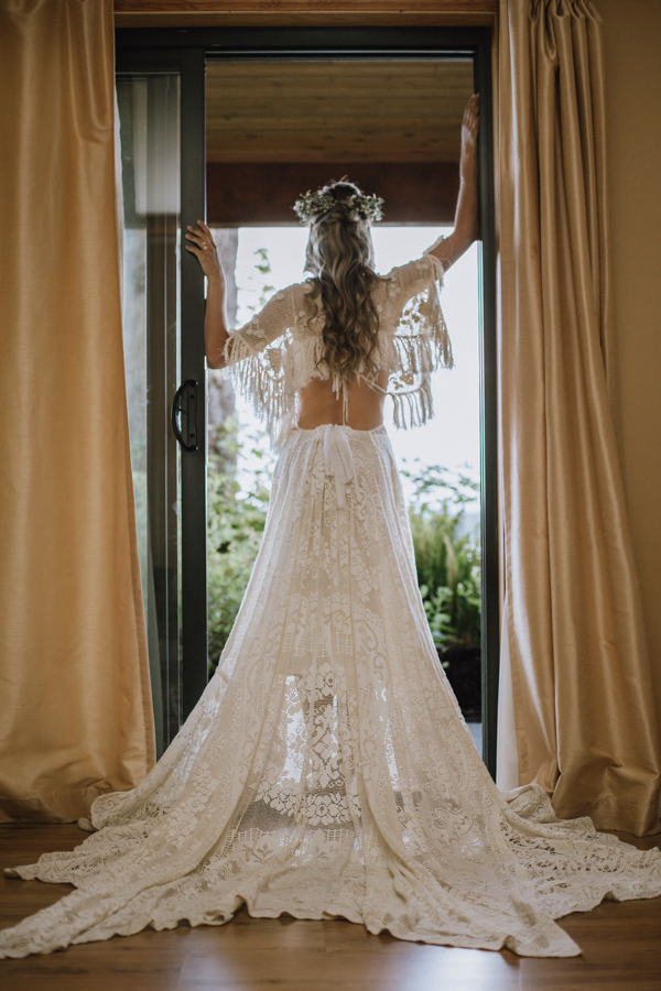 Bride looking out at ocean through window wearing stunning lace low back and flowing sleeves by Reclamation Design