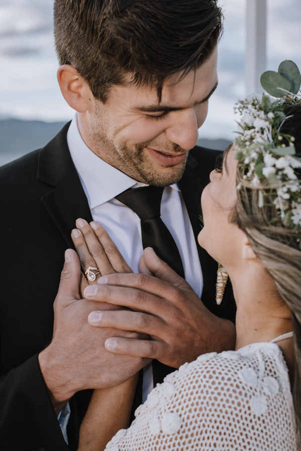 Groom holds bride's hand against his heart and smiles down at her by Gal Eye Photography