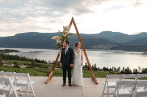 Couple on ceremony deck in front of wedding backdrop and lake in the Okanagan