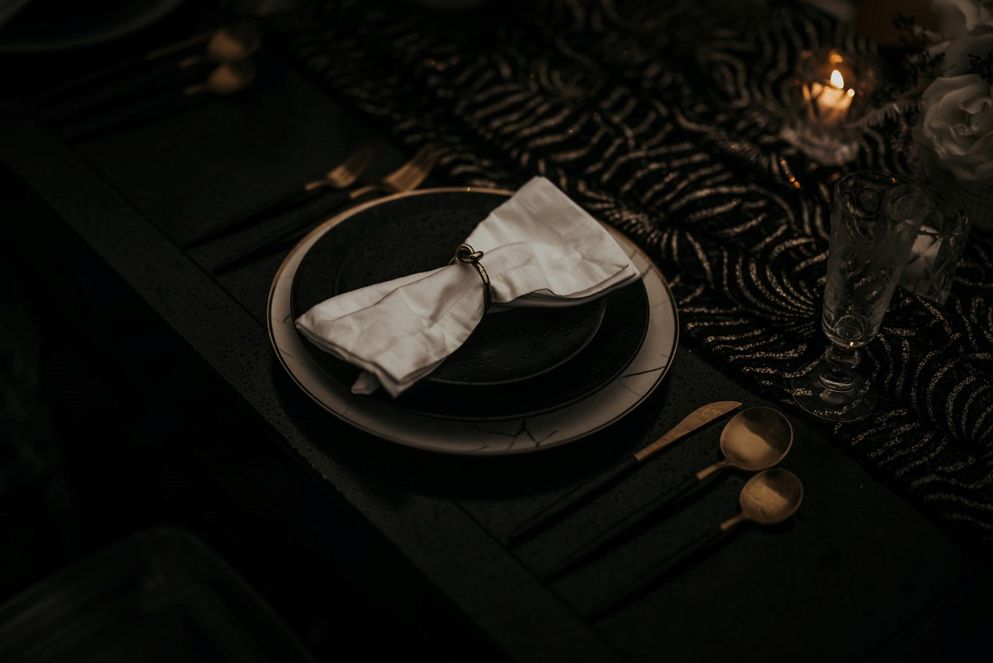 Black linen on table with black amd white settings and flowers with gold cutlery by The Proper Table Vancouver Island