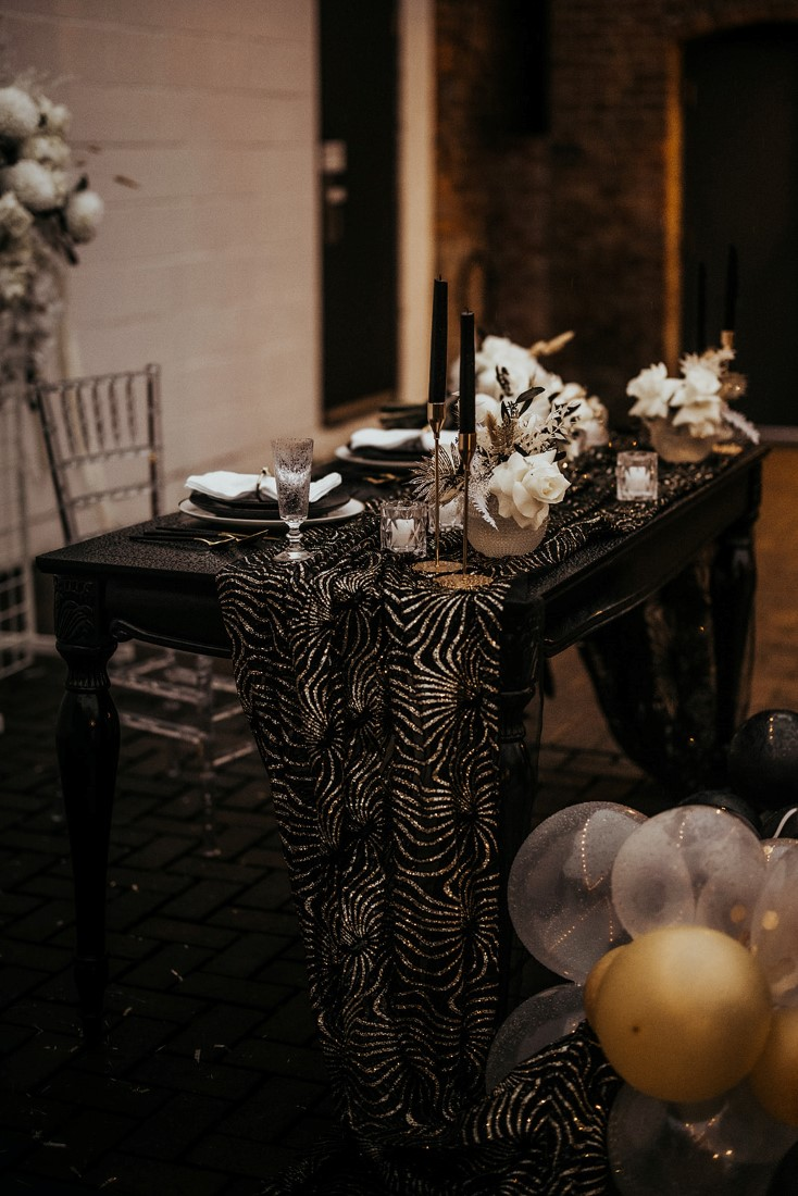 Sweetheart Table with black linens, gold cutler and white roses by En Vied Events