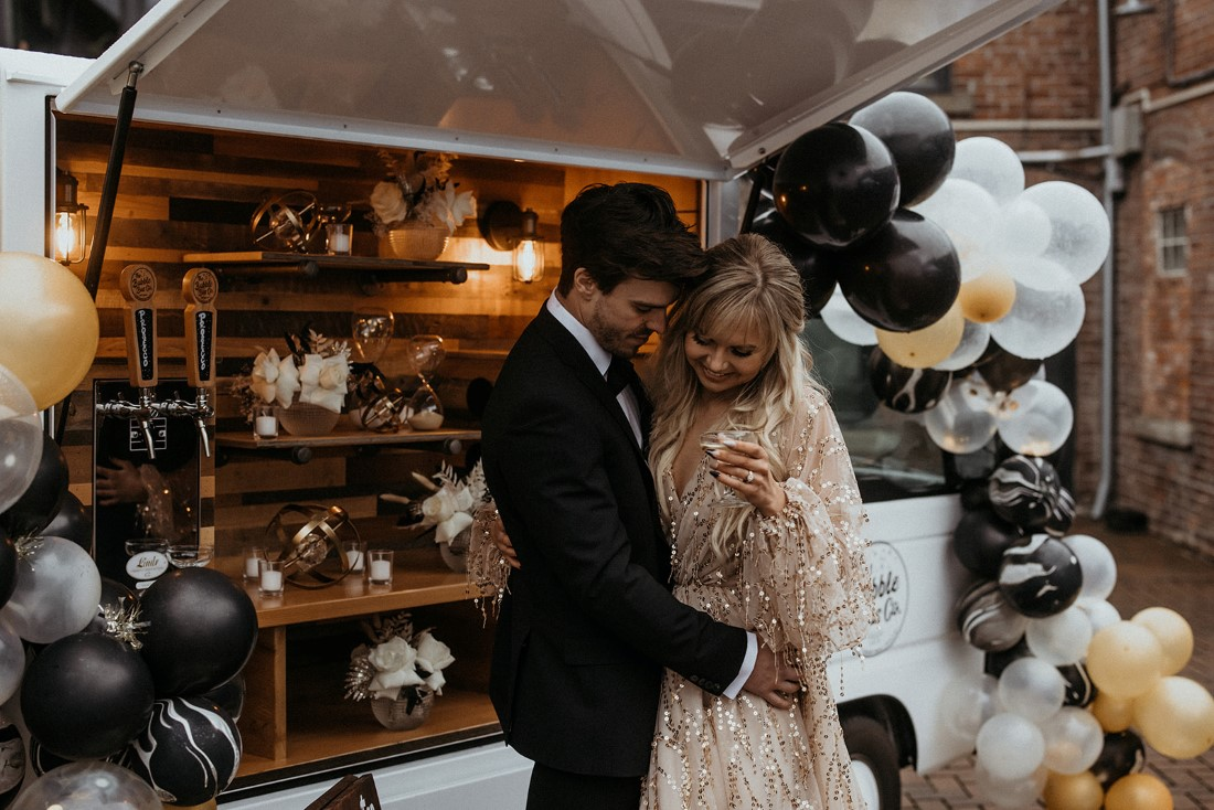 Valentine's Day Date in front of prosecco bubble bus with black, white and gold balloon garlands on Vancouver Island
