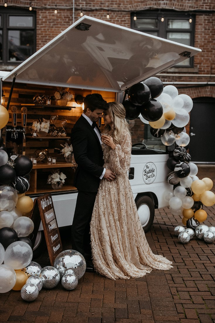 Glamorous couple enjoy personal moment sharing champagne in front of balloon garlands and bubble bus