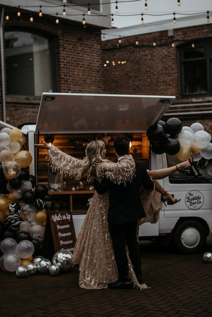 Couple twirl around drinking champagne in front of bubble bus co on Vancouver Island