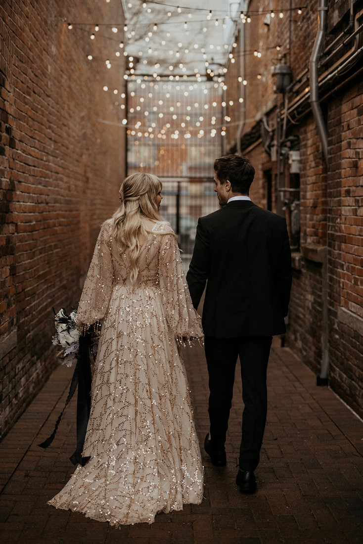 Romantic couple stroll through Vancouver Island alley wearing blush flitter gown and black suit with bowtie