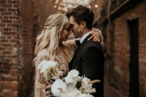 Newlyweds in Fan Tan Alley Vancouver Island hold white floral bouquet under cafe lights