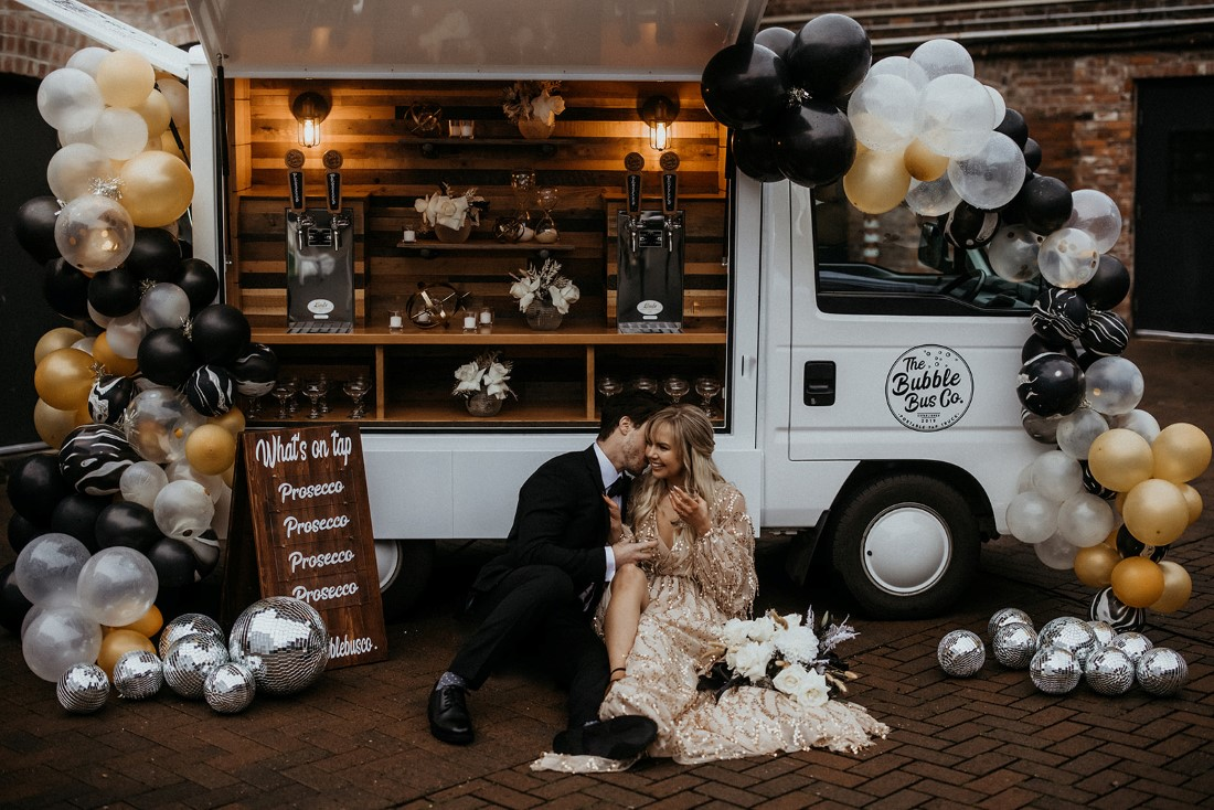 Romantic couple drinks prosecco in front of Bubble Bus Co Vancouver Island
