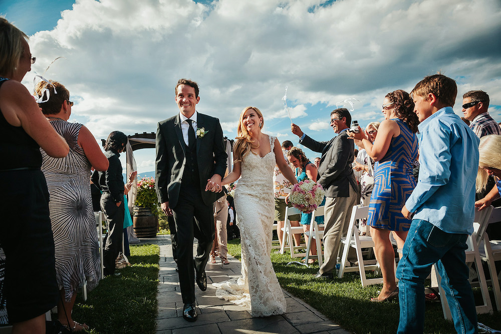 Newlyweds walk up the aisle smiling at guests at Summerhill Winery
