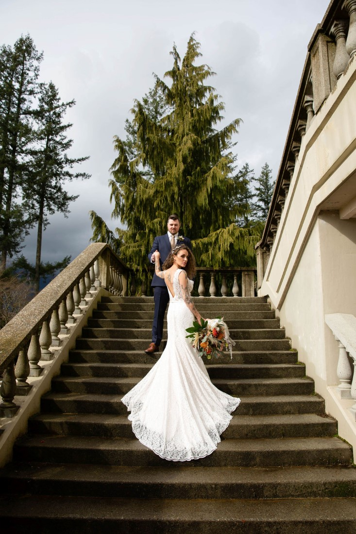 Newlyweds stand together on the stunning stairway at Swaneset Vancouver