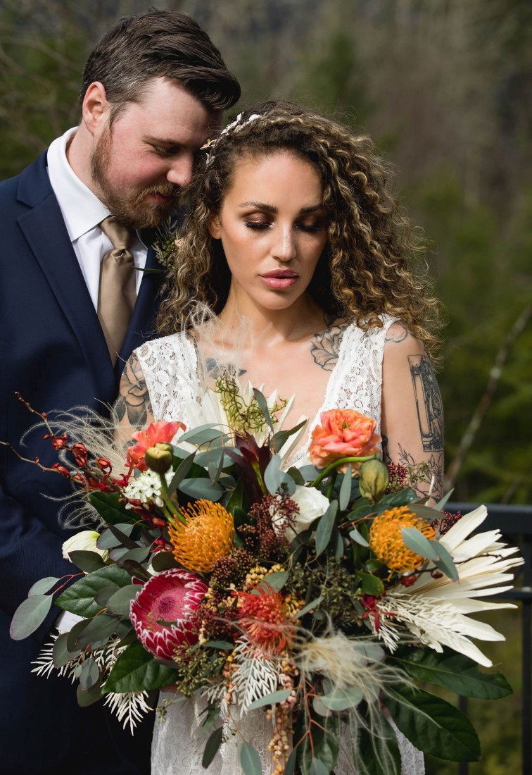 Bridal bouquet of pink protea, yellow mums, pampas grass, eucalyptus and white and peach roses by Maple Ridge Floral Ltd.