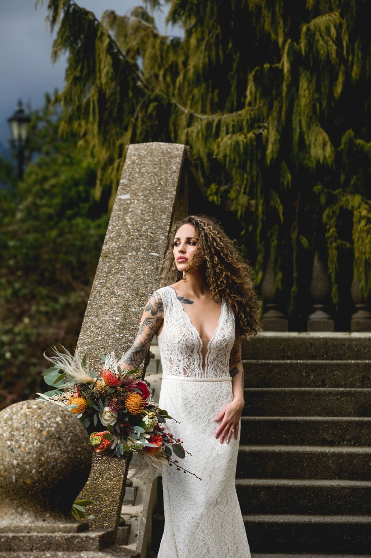 Bride in stunning gown with colourful bouquet stands on stairs of Swaneset Vancouver