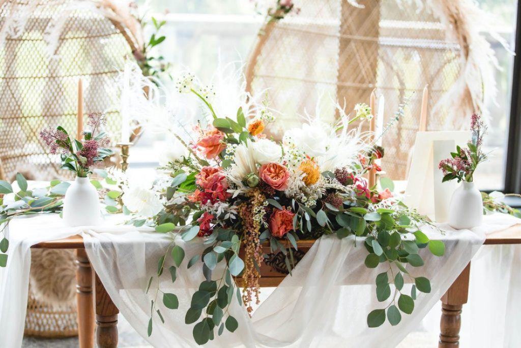 Florals on the front of sweetheart table feature eucalyptus, pampas grass, pink and peach roses by Maple Ridge Floral Ltd