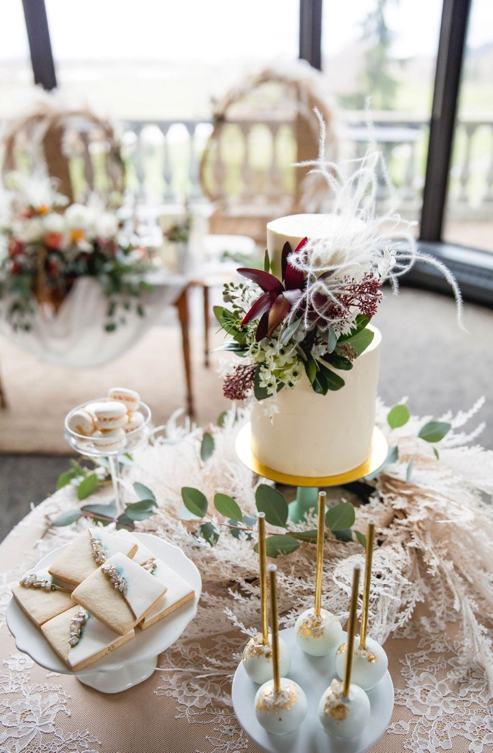 Wedding Cake with purple flowers sits on nuetral tone table by The Cake and the Giraffe Vancouver