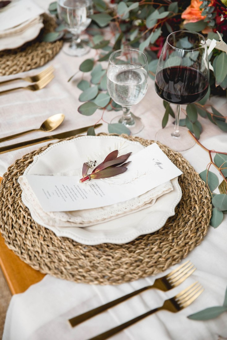 Flower sits on napkin on white plate and wisker charger by Wild Boheme Decor Vancouver