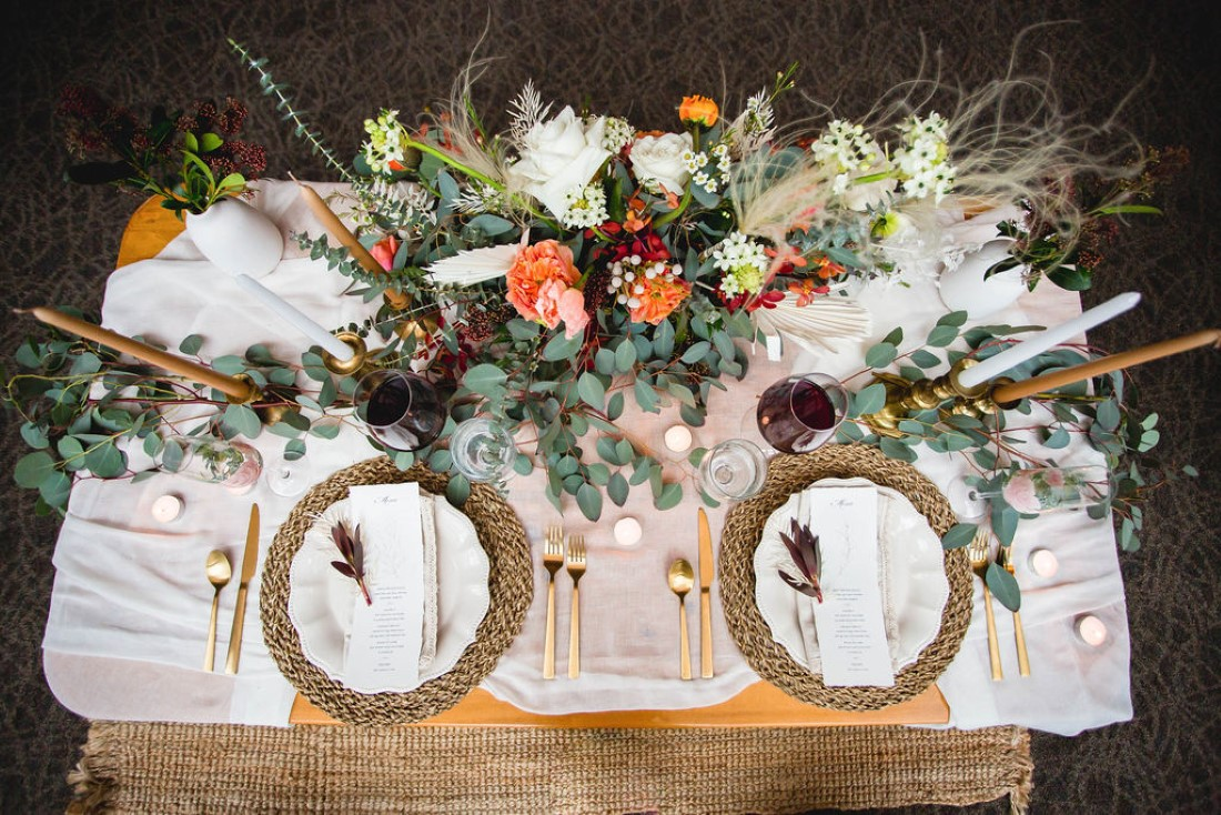 White plates on wicker place settings and flowers with pampas grass behind
