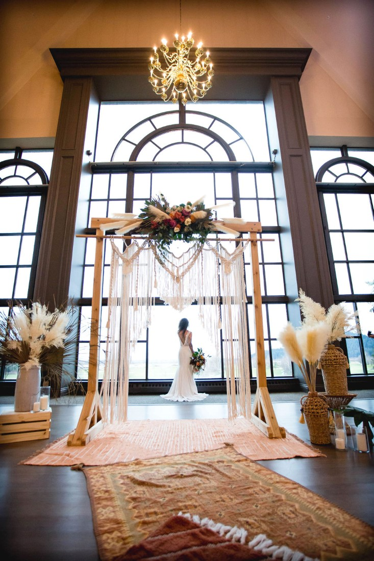 Bohemian Inspired Eleopement featuring rugs, pampas grass and backdrop in front of wall of windows at Swaneset Vancouver