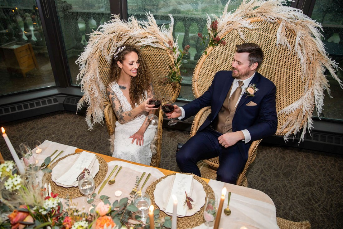Newlyweds sit in large wicker chairs edged in pampas grass in front of sweetheart table by Wild Boheme Decor