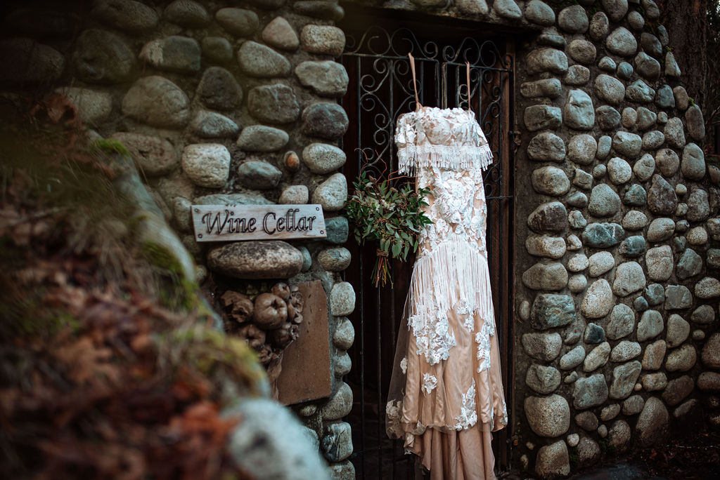 She Wore Flowers Bridal gown against stone wall at West Coast River Lodge on Vancouver Island
