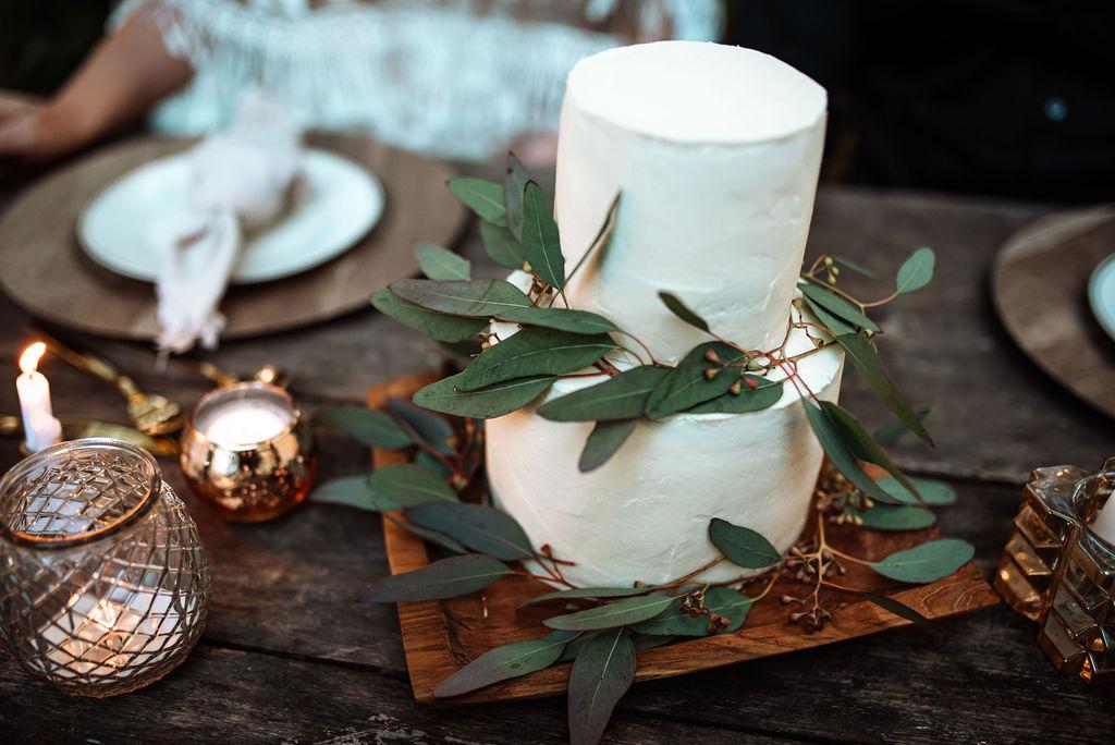 White wedding cake with eucalyptus leaves on west coast wood board