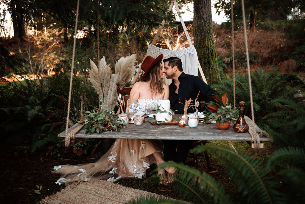 Triangle backdrop with hanging picnic board and newlyweds kissing