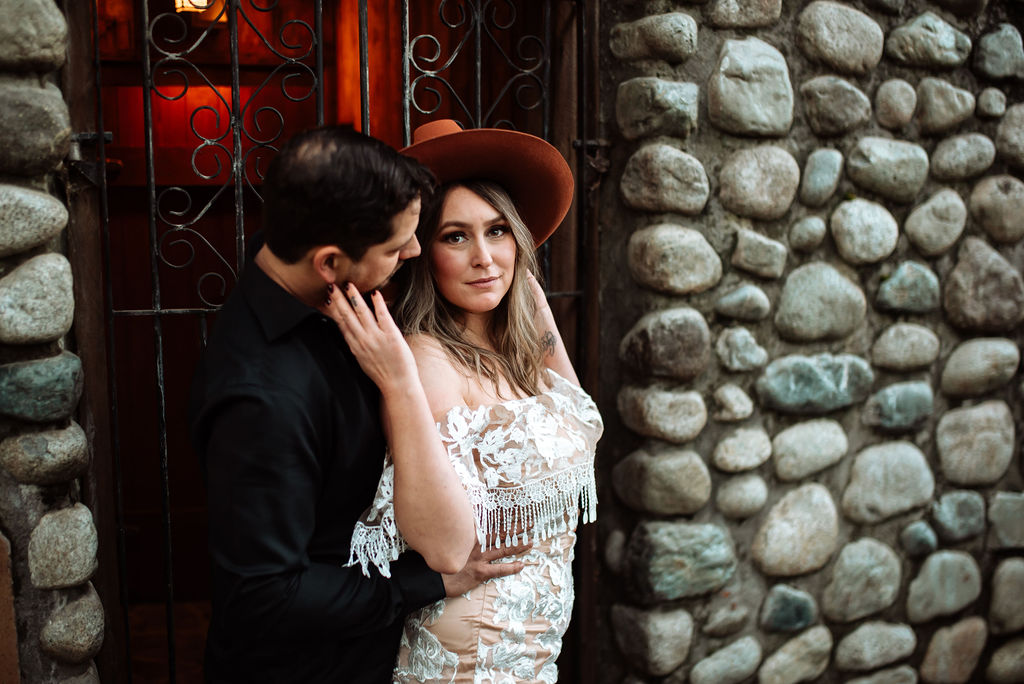 West Coast River Lodge newlyweds pose against stone wall on Vancouver Island