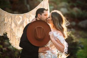 Newlyweds kiss behind brown velvet hat by Shop West Von Vancouver Island