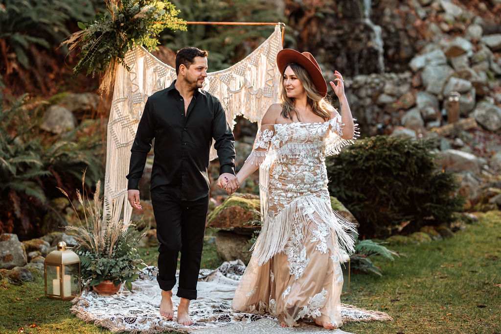 Bride and Groom hold hands and walk towards picnic