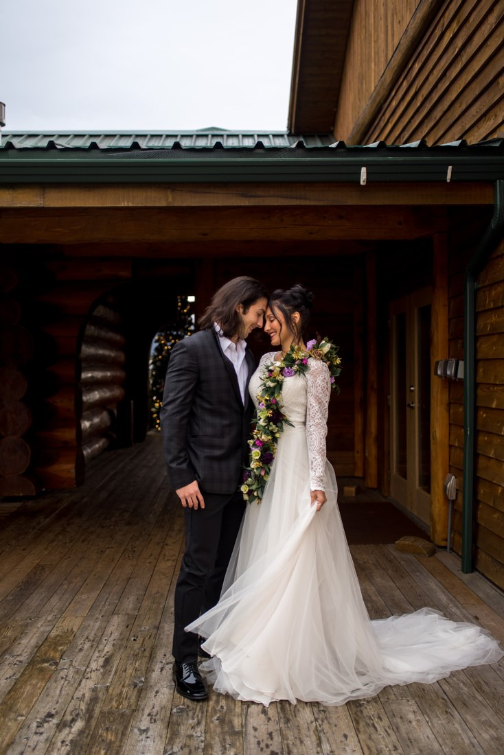 Cozy Elopement Inspiration newlyweds in front of Fraser River Lodge