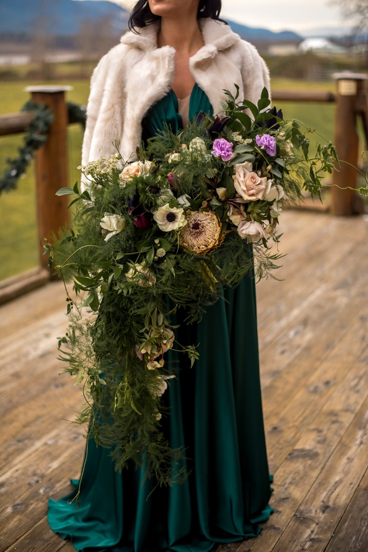 Bride in green gown holds bouquet of anemones, roses and greenery by All Her Flowers Fraser Valley